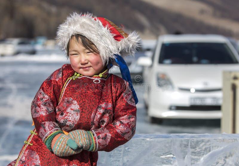 Iklädda traditionella kläder för mongolisk flicka på en djupfryst sjö arkivbild