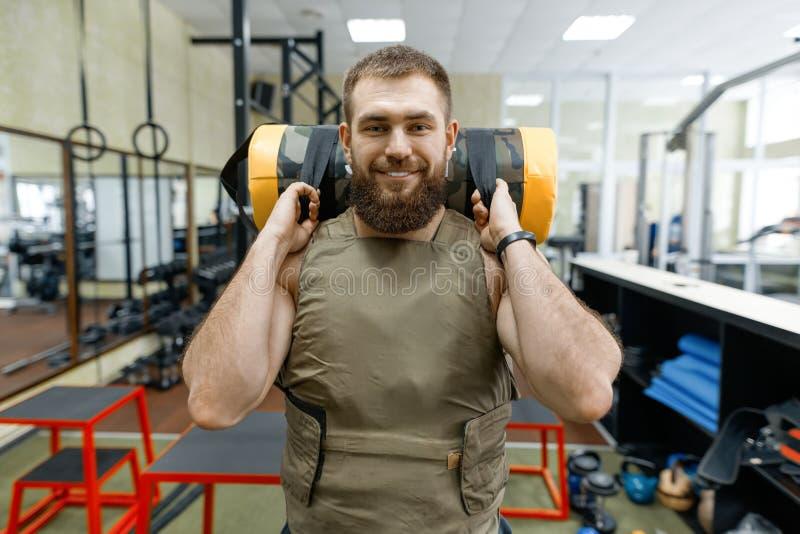 Iklätt för man för stående tilldelar muskulöst vägt caucasian skäggigt idrottshallen, militär stil arkivfoton