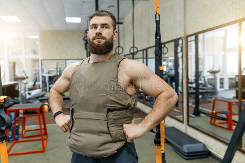 Iklätt för man för stående tilldelar muskulöst vägt caucasian skäggigt idrottshallen, militär stil fotografering för bildbyråer