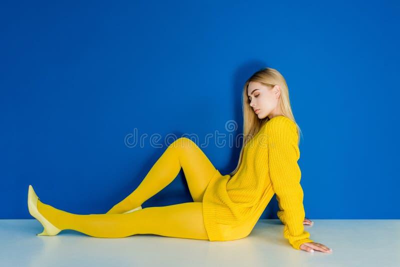 Iklätt gult sammanträde för elegant blond kvinna på golv royaltyfri foto