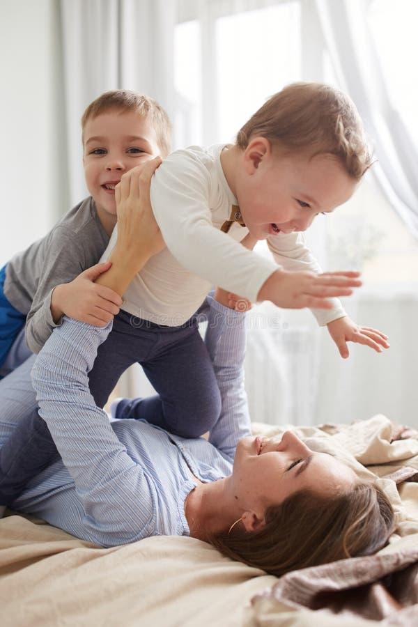 Iklätt ljust för härlig ung moder - den blåa pajamaen och hennes två lilla söner har gyckel på sängen i den ljusa slags tvåsittss arkivfoton