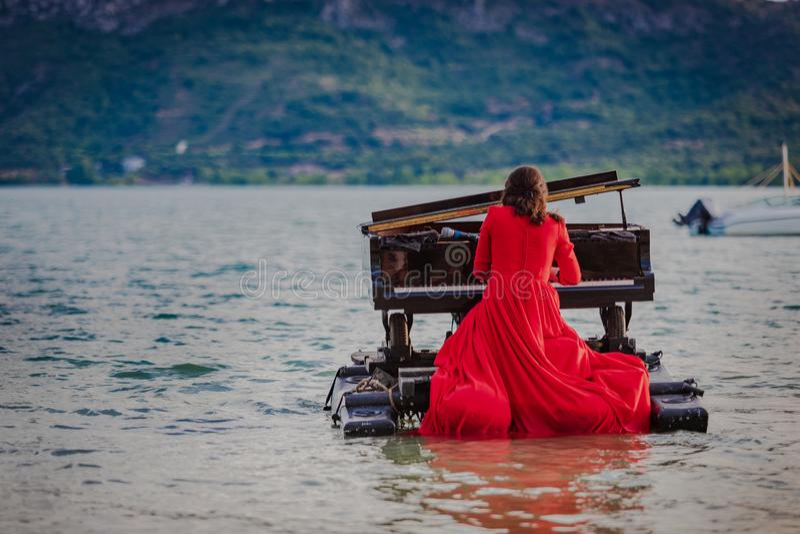Iklätt rött för kvinna spela pianot på en sjö royaltyfria bilder