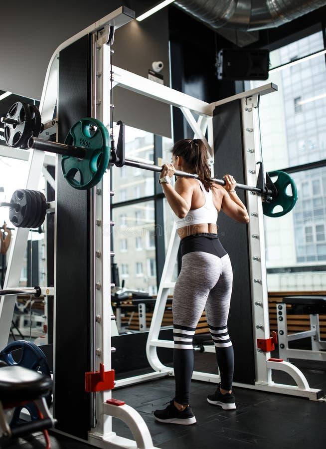 Ikl?dda sportswearsquats f?r ung idrotts- flicka med en skivst?ng i den moderna idrottshallen royaltyfria bilder