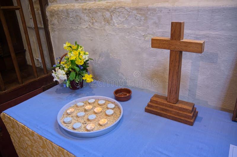 Ikonenhaftes hölzernes Kreuz mit Kerzen u. Blumen lizenzfreie stockfotografie