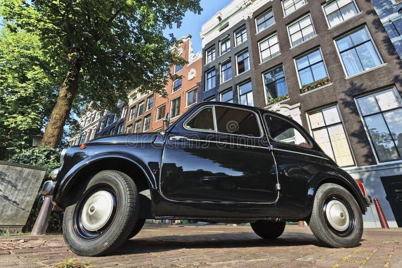 Ikonowy Fiat 500 przeciw antycznym gabled domom w Amsterdam obraz stock