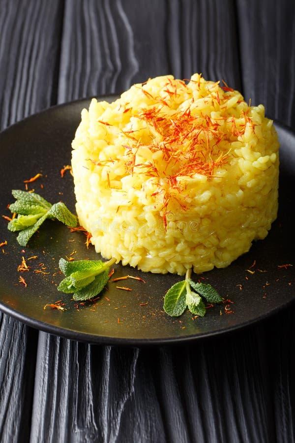 Il alla tradizionale del risotto milanese con zafferano è decorato con immagine stock