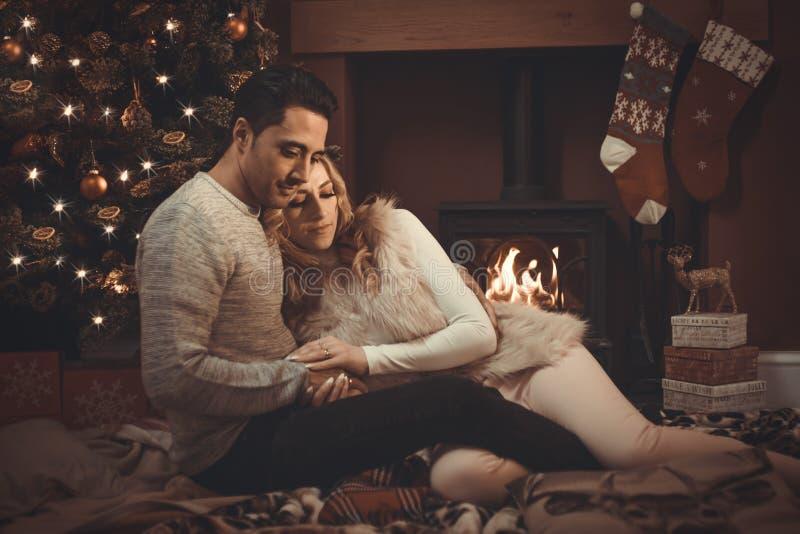 Il amore si accoppia dal fuoco di ceppo al Natale fotografie stock libere da diritti