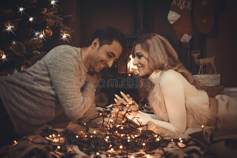 Il amore si accoppia dal fuoco di ceppo al Natale fotografia stock libera da diritti