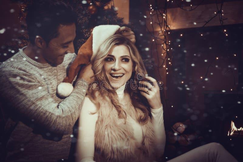 Il amore si accoppia dal fuoco di ceppo al Natale immagine stock
