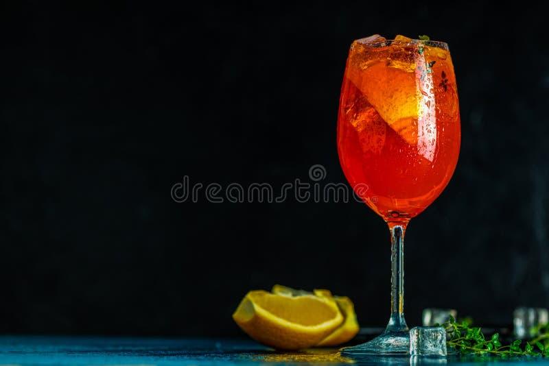 Il aperol del cocktail spritz in grande vetro di vino con le gocce di acqua su fondo scuro Cocktail dell'alcool di estate con le  fotografia stock libera da diritti
