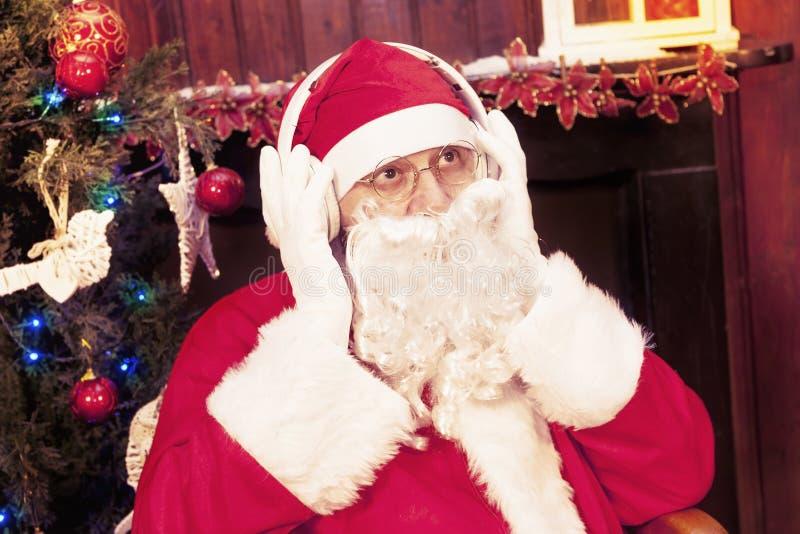 Il Babbo Natale che ascolta la musica sulle cuffie immagini stock libere da diritti
