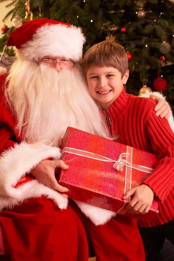 Il Babbo Natale che dà regalo al ragazzo immagine stock libera da diritti