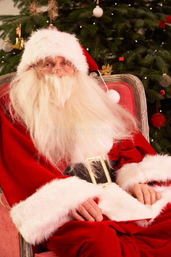 Il Babbo Natale che si siede in poltrona fotografia stock libera da diritti