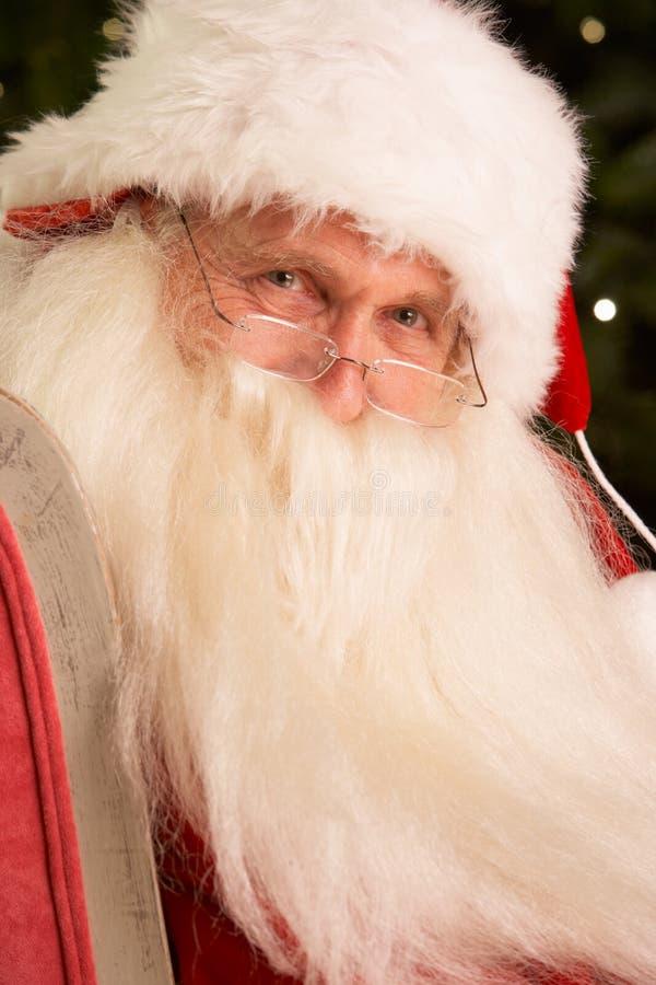 Il Babbo Natale che si siede in poltrona fotografia stock