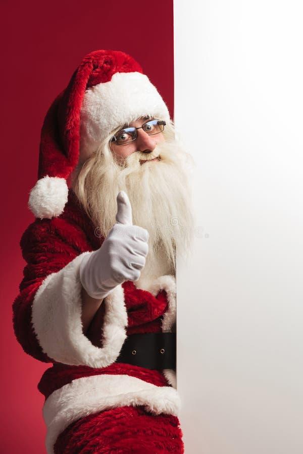 Il Babbo Natale che si siede vicino al bordo in bianco e fa il segno giusto fotografia stock