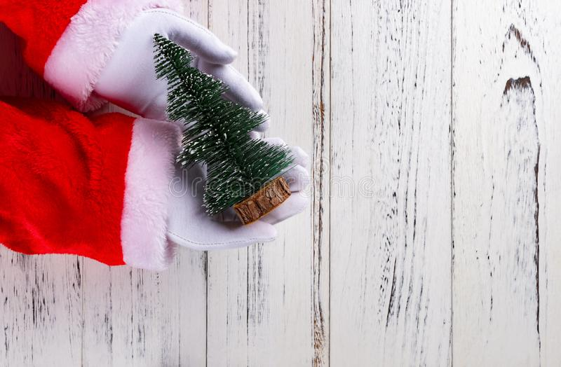 Il Babbo Natale che tiene un modello dell'albero di Natale su fondo di legno bianco fotografia stock libera da diritti