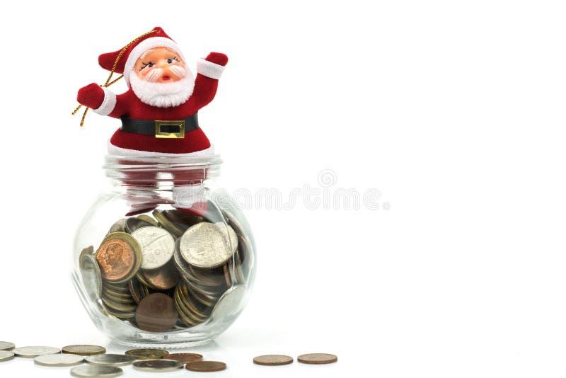 Il Babbo Natale ed i soldi conia in vetro isoalted su backgroun bianco immagini stock