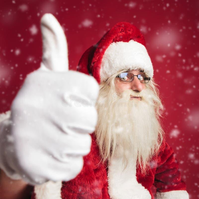 Il Babbo Natale emozionante che fa il segno giusto mentre nevicando fotografia stock