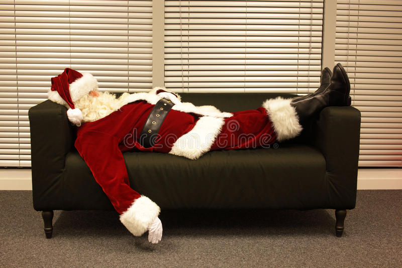Il Babbo Natale esaurito che dorme sul sofà fotografia stock