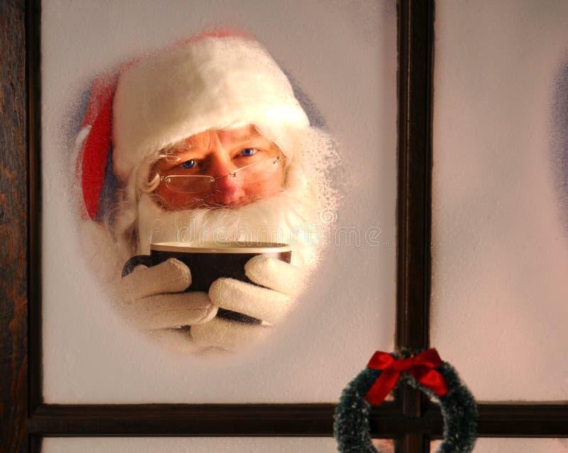 Il Babbo Natale in finestra con la tazza fotografia stock