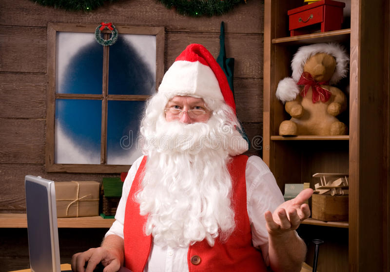 Il Babbo Natale in workshop con il computer portatile fotografia stock