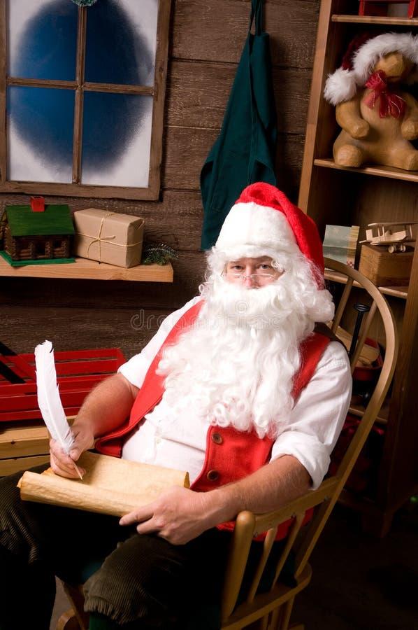 Il Babbo Natale in workshop con la lista immagini stock libere da diritti