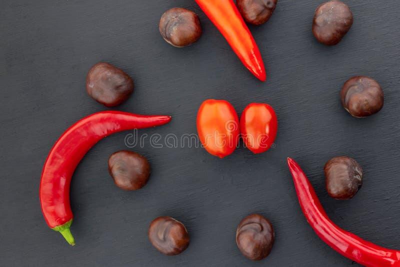 Il baccello rovente del pepe ha arricciato verdura rossa del cerchio della frutta della castagna del pomodoro marrone delle coppi immagine stock