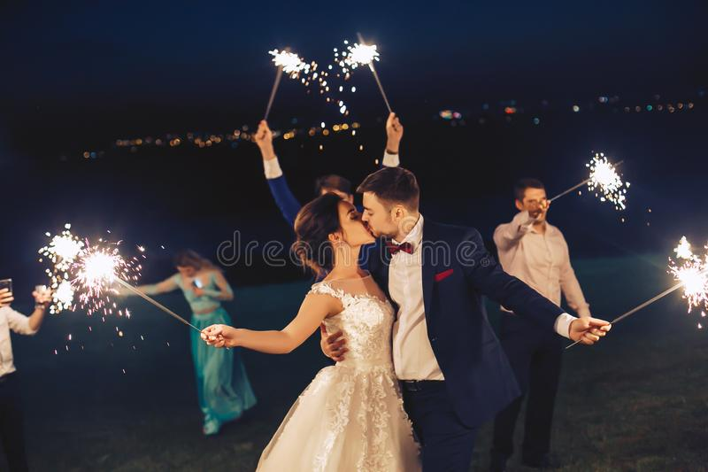 Il bacio delle persone appena sposate e tiene la stella filante immagini stock libere da diritti