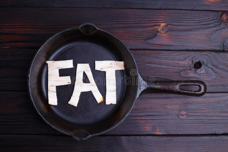 Il bacon ha modellato come il grasso di parola nella padella Dieta, nutrizione, immagine stock