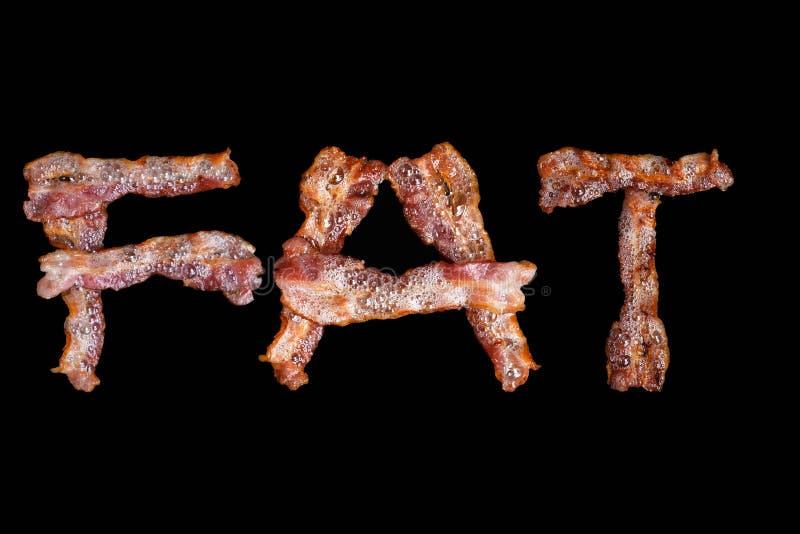 Il bacon ha modellato come la parola FAT su fondo nero fotografia stock libera da diritti