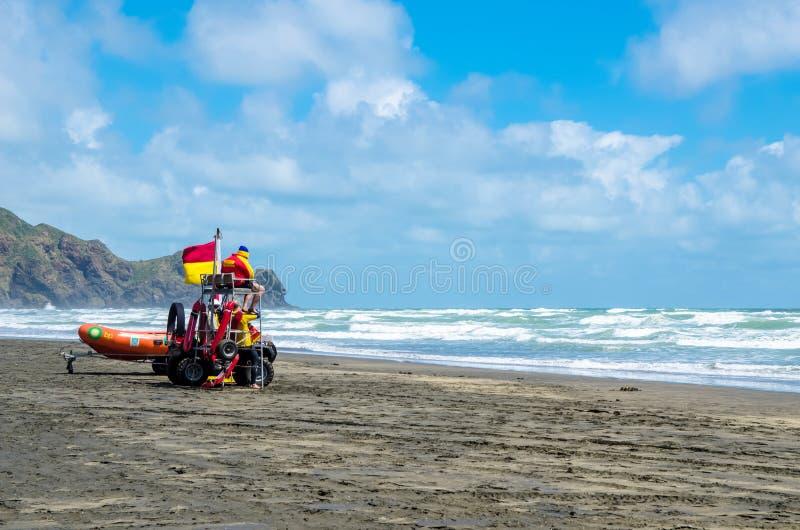 Il bagnino può appoggio visto sulla spiaggia sorveglia la sicurezza ed il salvataggio dei nuotatori e dei surfisti in Te Henga Be immagine stock