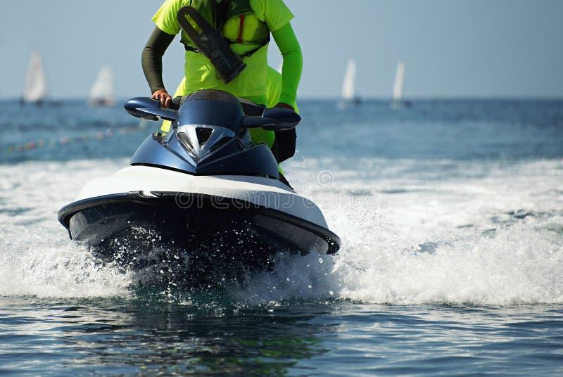 Il bagnino su un jet ski sorveglia la spiaggia fotografie stock