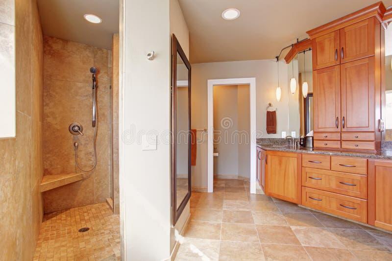 Il bagno di lusso con la grande combinazione di stoccaggio ed apre la doccia immagini stock libere da diritti