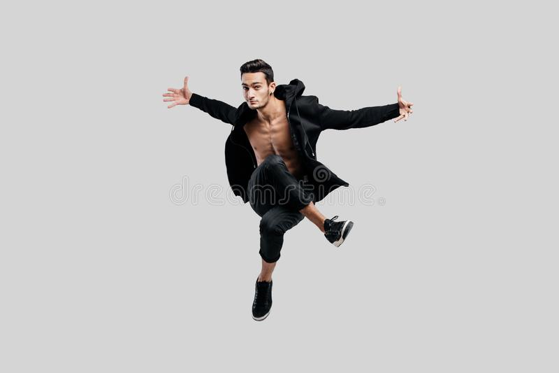 Il ballerino bello della via che balla vestito in pantaloni neri ed in una maglietta felpata su un torso nudo salta e sparge le s fotografia stock libera da diritti