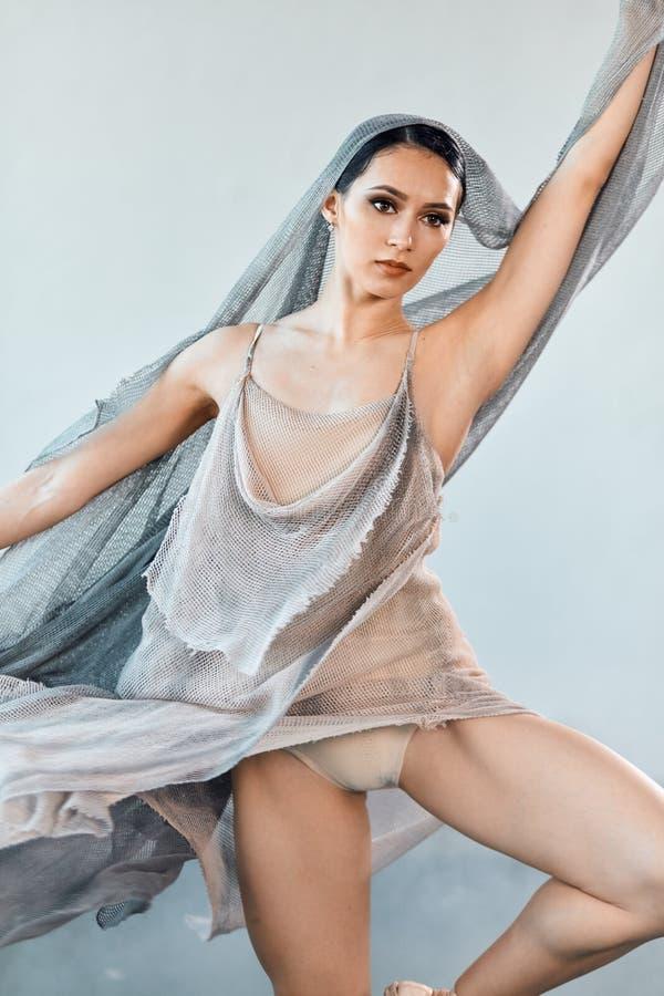 Il ballerino di balletto flessibile che allunga nello scuro ha acceso lo studio immagini stock libere da diritti