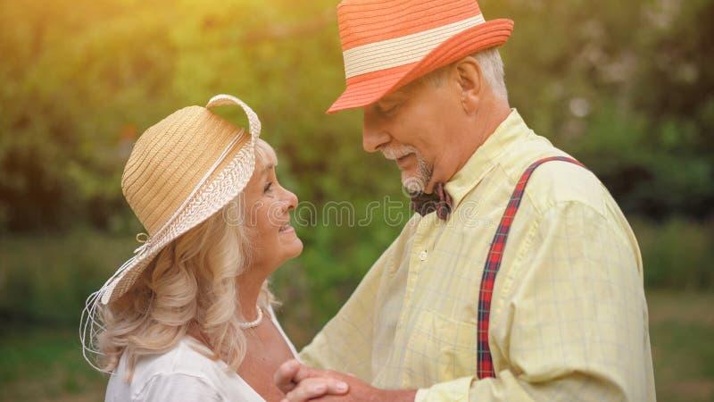 Il ballo di vecchie coppie nel giardino di estate fotografia stock libera da diritti