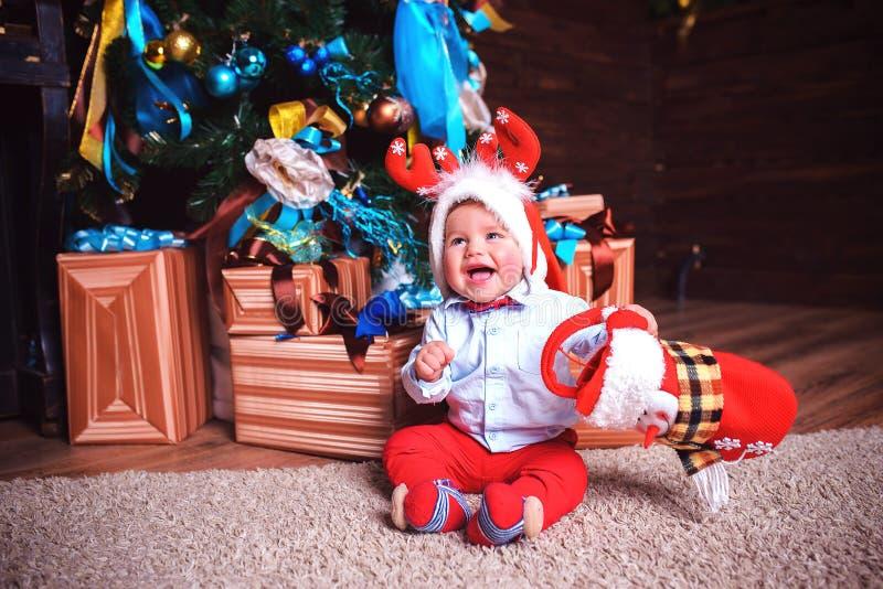 Il bambino è felice un giorno festivo vicino all'albero di Natale fotografia stock