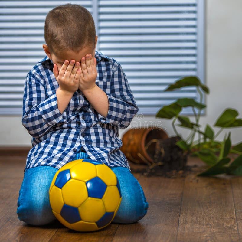Il bambino è impaurito della punizione Ha fracassato il vaso di fiore immagine stock libera da diritti