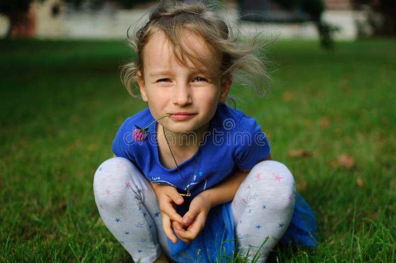 Il bambino è occupante ed esaminante la macchina fotografica Gli occhi del ` s della ragazza restretti ironicamente Tiene un fior fotografia stock libera da diritti