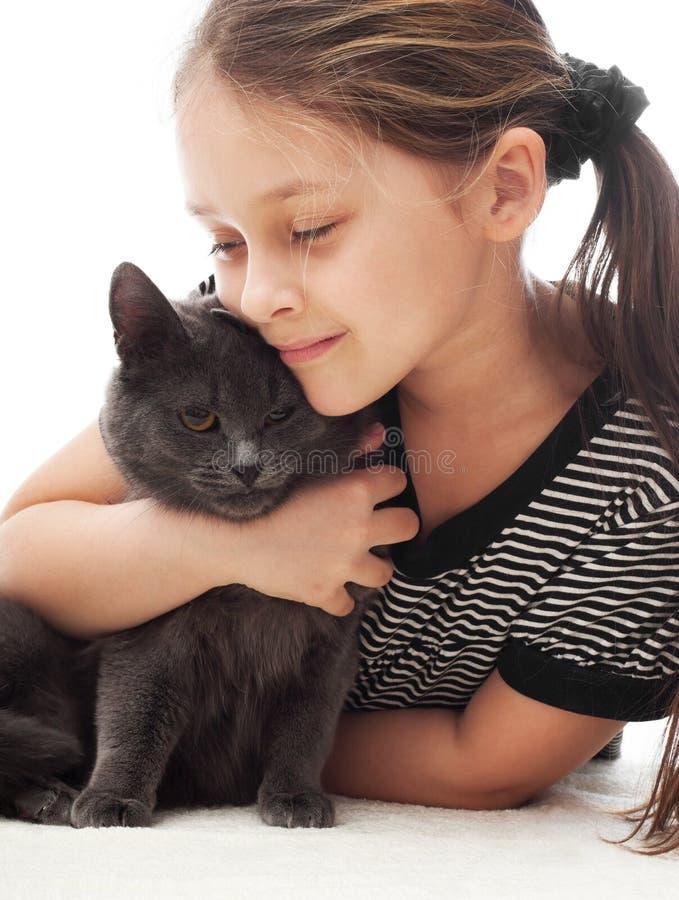 Il bambino abbraccia delicatamente il gatto fotografie stock