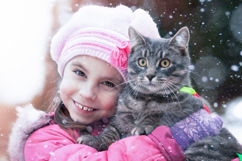 Il bambino abbraccia un gatto nella via nell'inverno fotografie stock