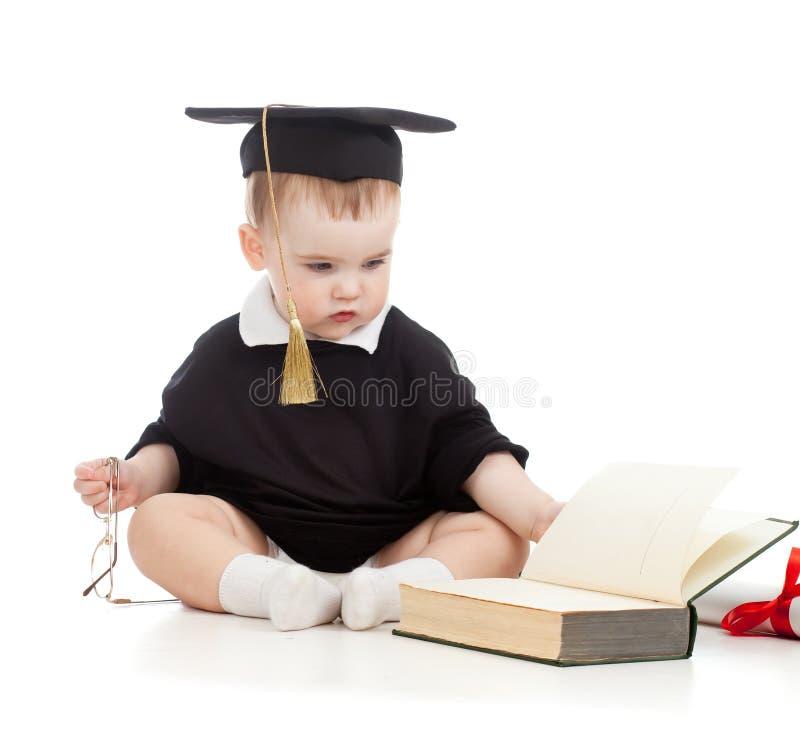 Il bambino in accademico copre con i vetri ed il libro immagini stock