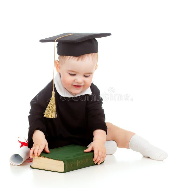 Il bambino in accademico copre con rullo ed il libro fotografia stock libera da diritti
