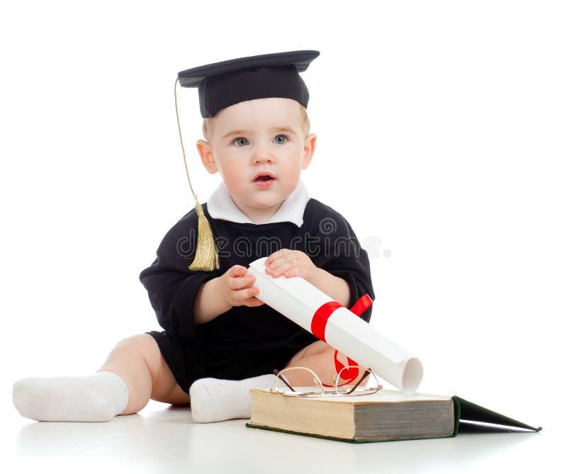 Il bambino in accademico copre con rullo ed il libro fotografie stock libere da diritti