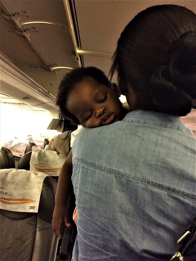 Il bambino africano sta dormendo sulla spalla della madre fotografie stock libere da diritti