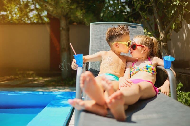 Il bambino amoroso delle coppie scherza su una chaise-lounge dallo stagno di estate immagine stock libera da diritti