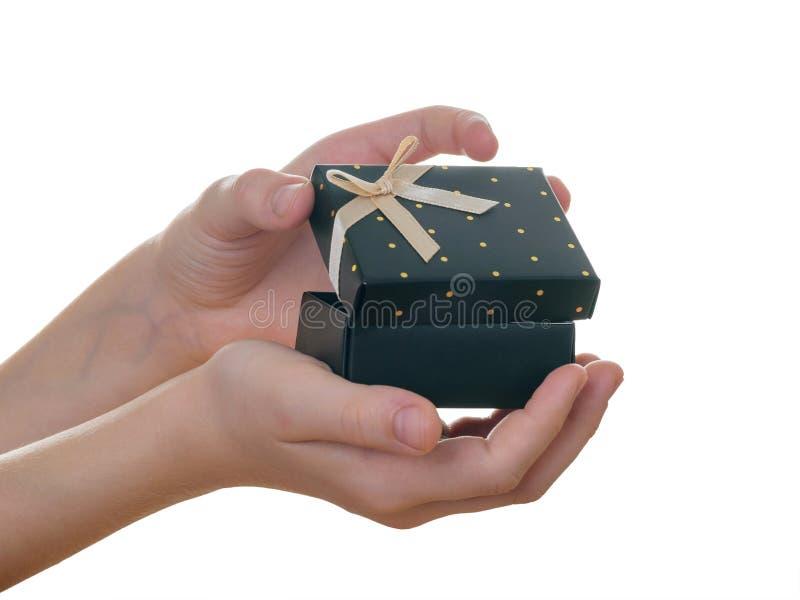 Il bambino apre la scatola nera delle mani con il nastro dorato isolato su fondo bianco fotografie stock libere da diritti