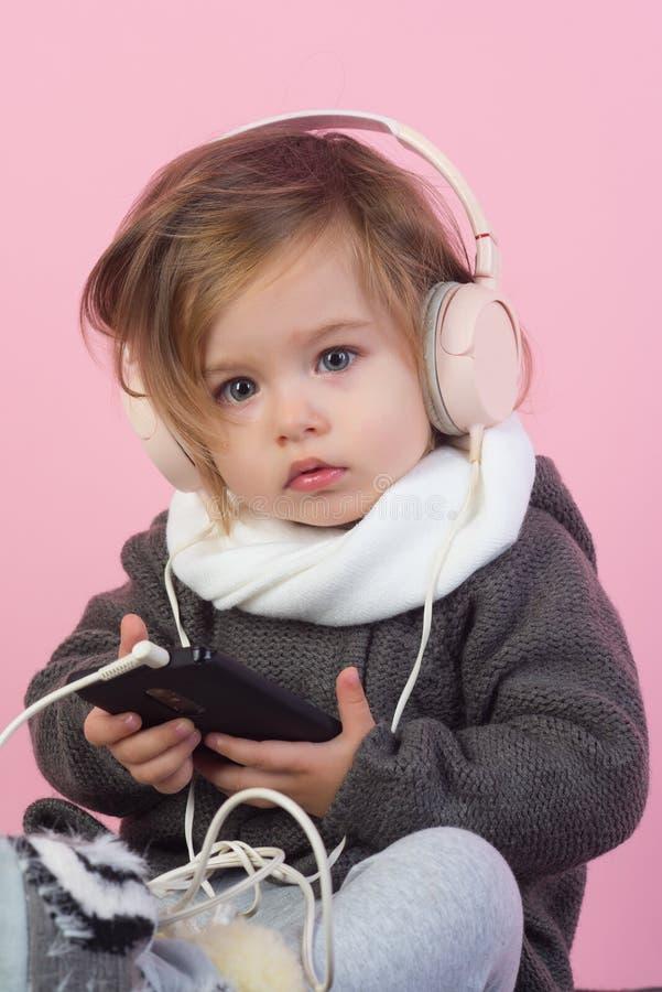 il bambino ascolta musica con la cuffia avricolare ed il mp3 sul telefono Avere divertimento modo del bambino di inverno Piccola  fotografia stock