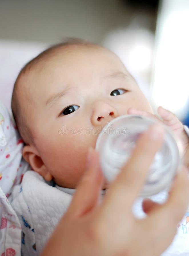 Il bambino asiatico è latte alimentare immagine stock