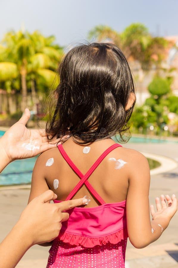 Il bambino asiatico che usando la lozione di Sunblock lei indietro pela prima di Swimmi immagini stock libere da diritti